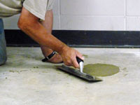 Repairing the cored holes in the concrete slab floor with fresh concrete and cleaning up the Jasper home.