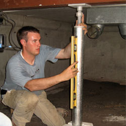 A contractor in Fort Knox installing a crawl space jack post.