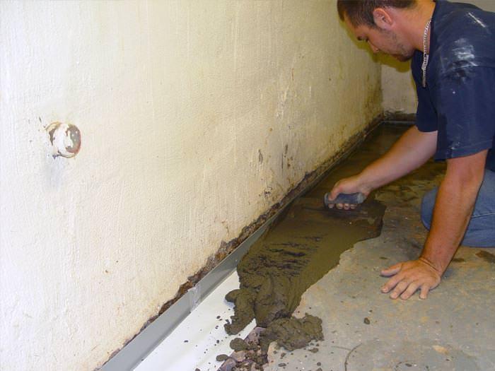 A Basement Waterproofer Installing Perimeter Drain System In Huntingburg