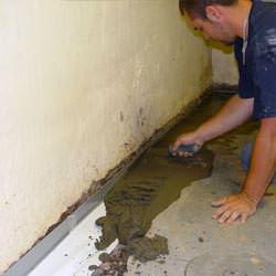 A basement waterproofer installing a perimeter drain system in Marion